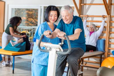 nurse helping elder man in hospital gym.