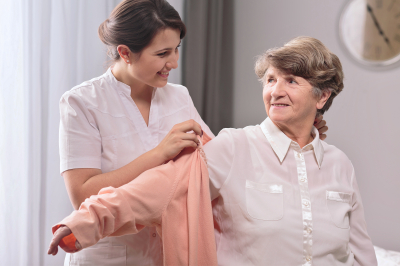 Helpful young caregiver giving the sweater to older woman