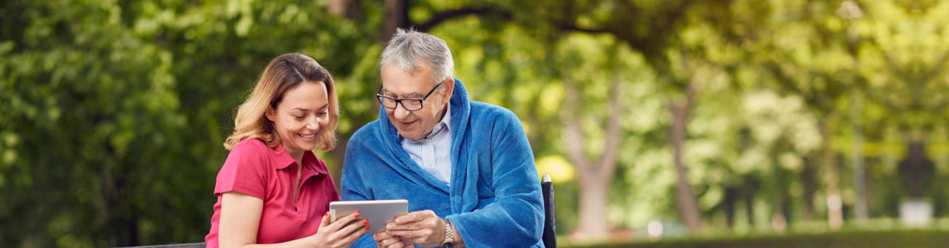 senior man with his caregiver smiling while reading